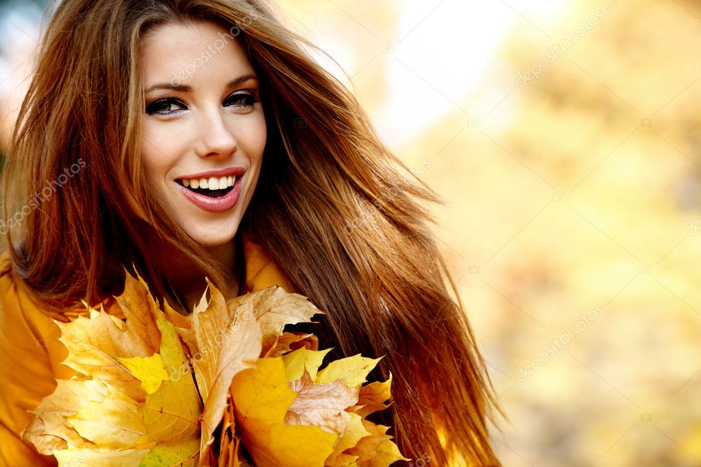 Young woman in autumn orange leaves. Outdoor.