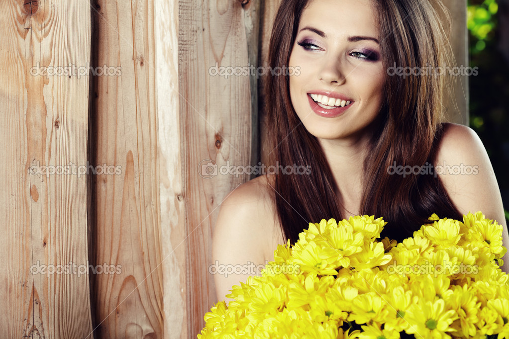 Closeup portrait of cute young girl with yellow flowers smiling