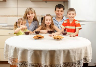 Happy family drinks tea