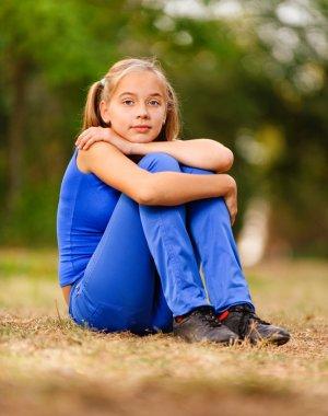 Teenage girl sitting on green meadow