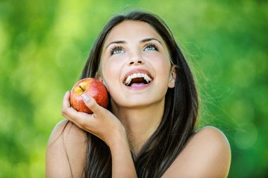 Woman holding an red apple and smiling