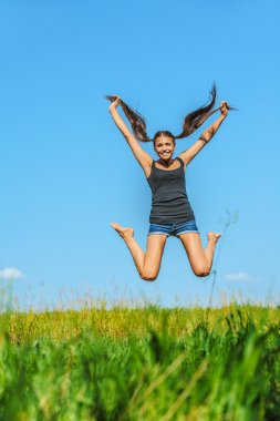 Beautiful woman jumps high into sky
