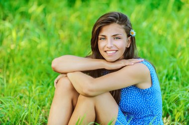 Woman sitting on grass and smiling