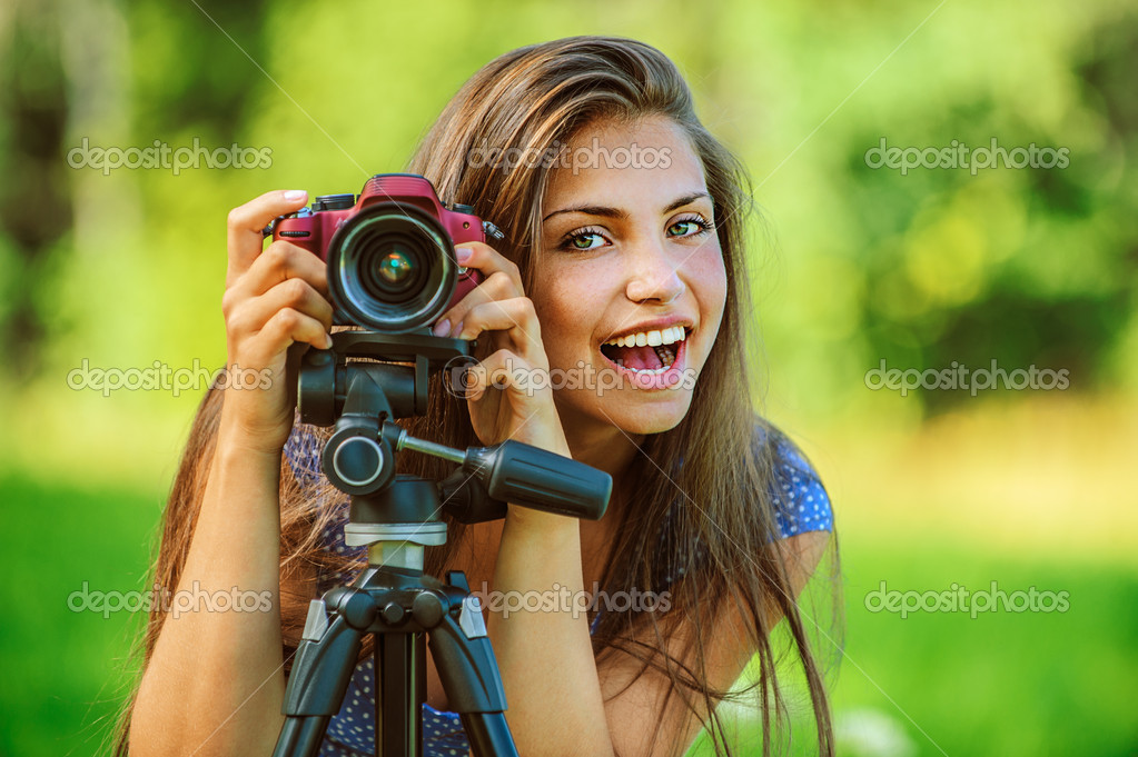 Beautiful woman photographed with camera tripod