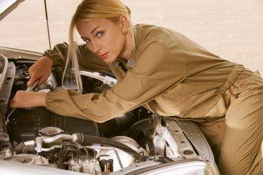 Young woman repairing car