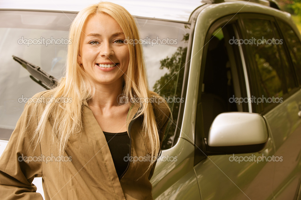Young woman smiling about car