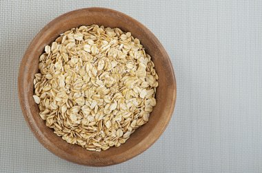 Rolled oats in a wooden bowl on a gray cloth.