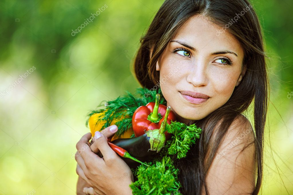 Woman with bare shoulders holding vegetable