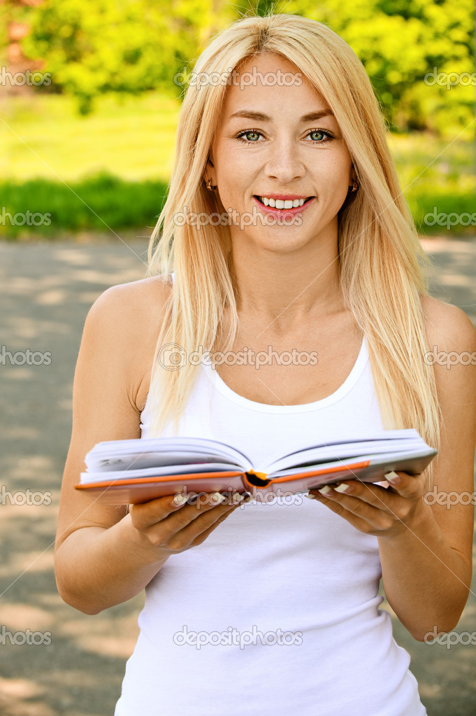 Young smiling woman reading book
