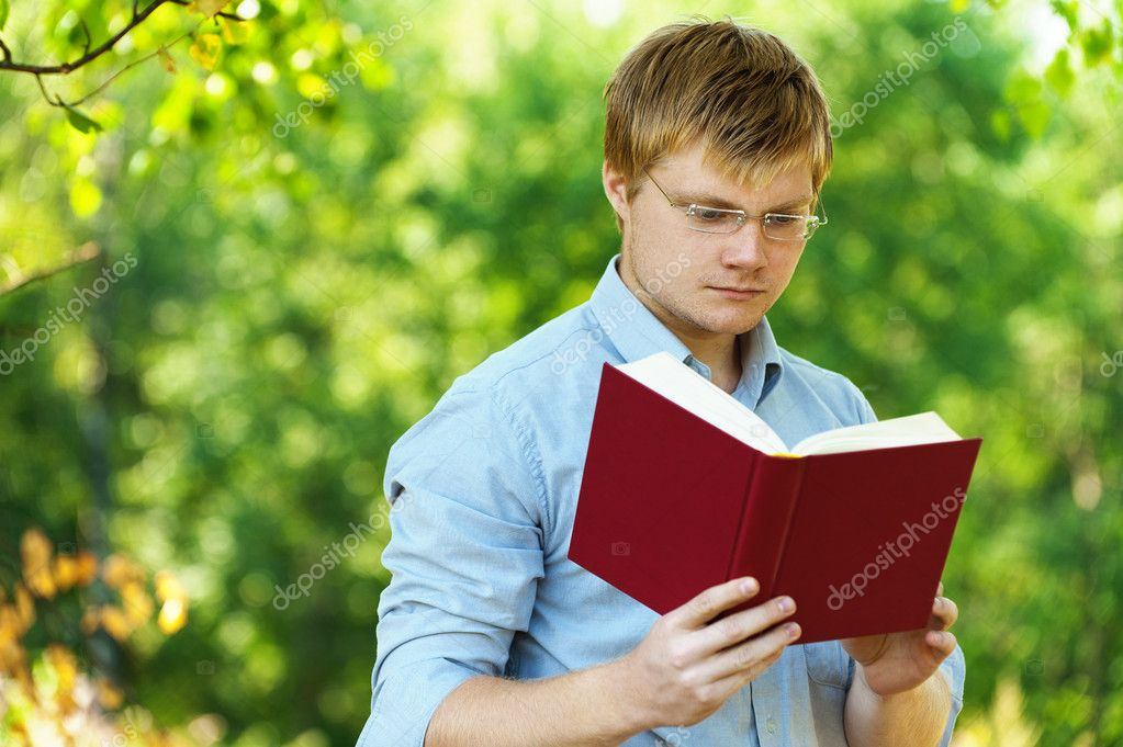 Student (male) with glasses reading book