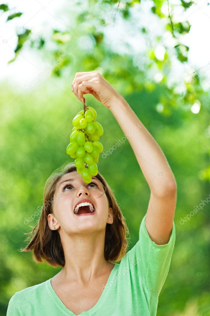 Portrait of woman with bunch of green grapes