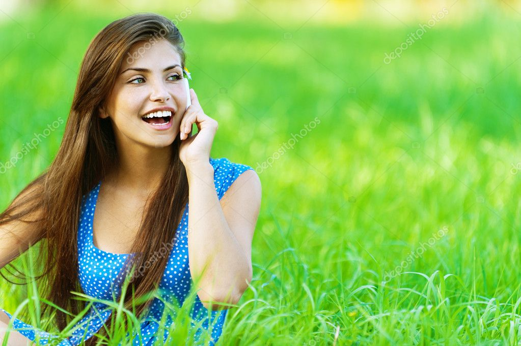 Young beautiful woman in blue dress sitting on grass in summer city park an