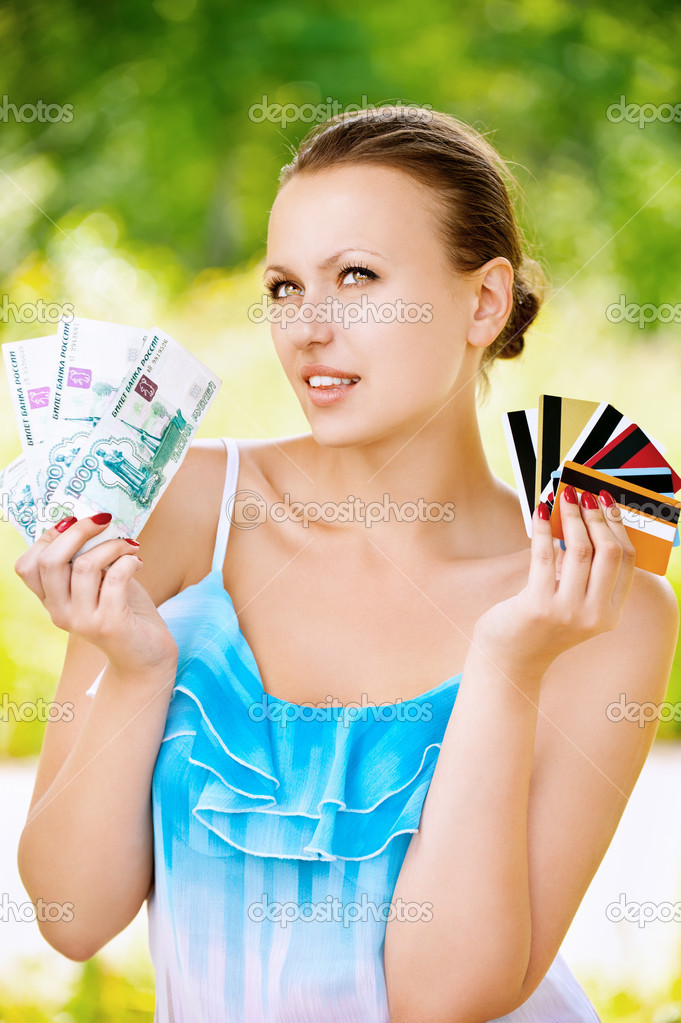 Woman holding credit cards and cash