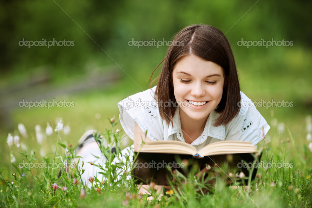 Young woman lies on grass and reads book
