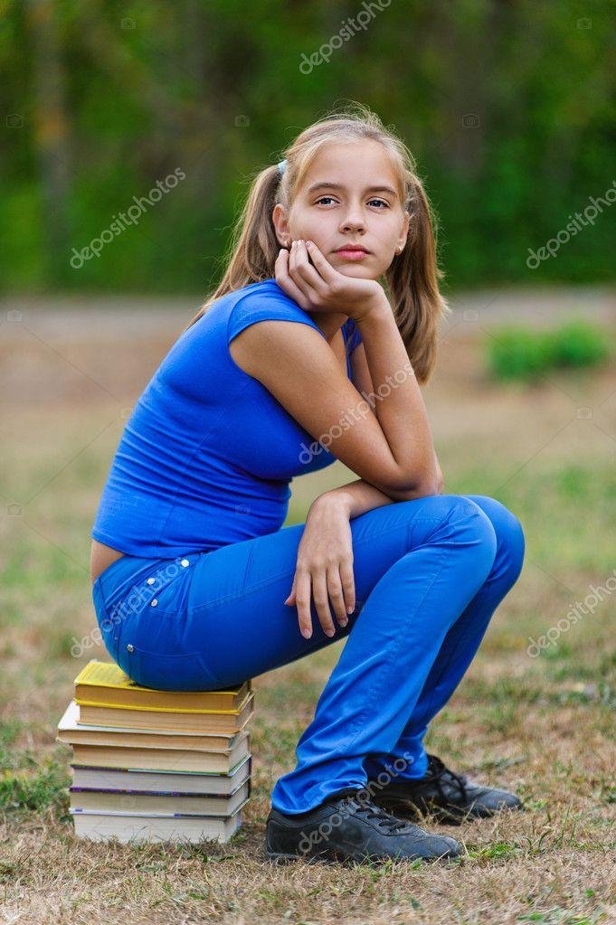 Teenager girl sitting on stack books