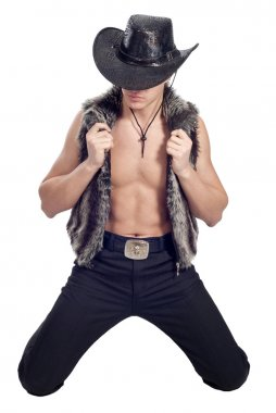 Young handsome man posing in studio in cowboy's hat