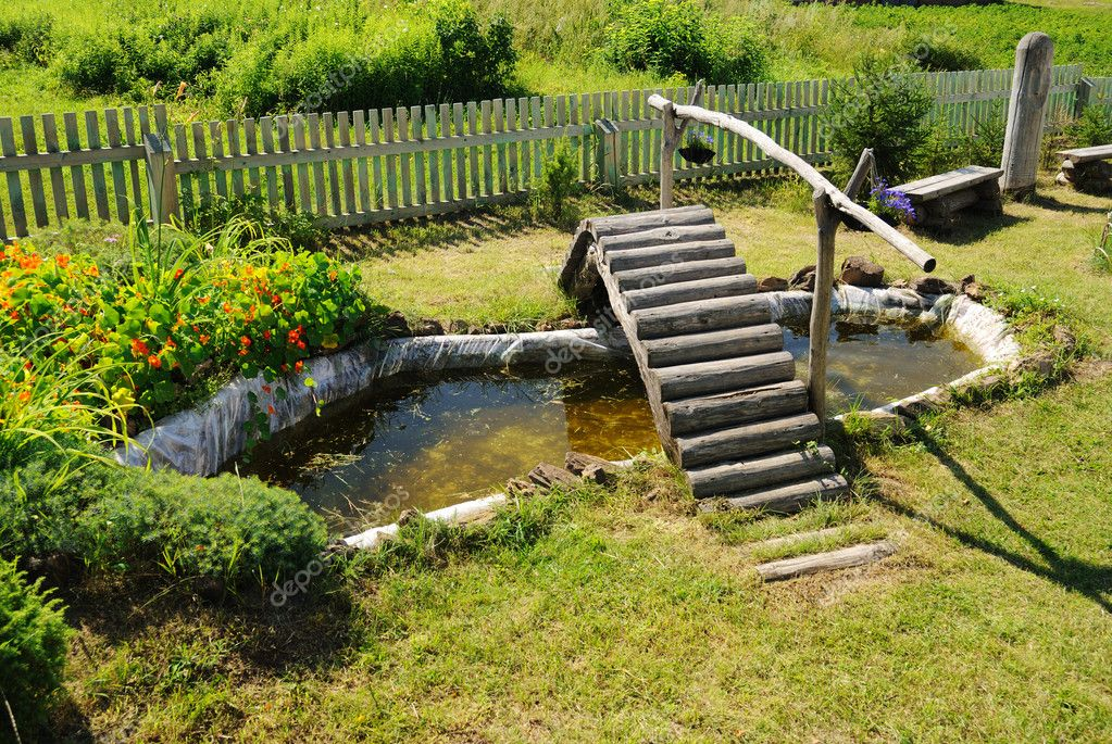 Small garden pond with wooden bridge