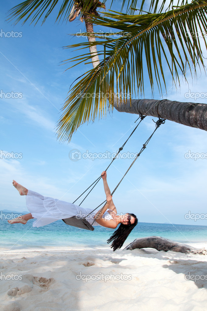 Young woman on the swing on the beach in white dress
