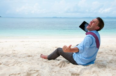 Happy business man sitting and working on the beach with tablet