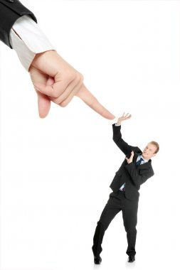 Scared young businessman afraid of big hand