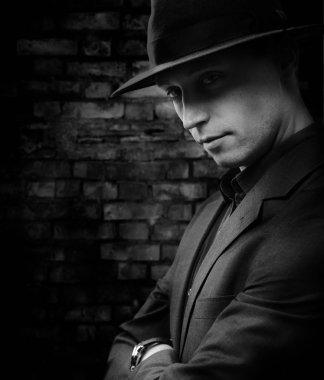 Man with hat standing against dark brickwall background
