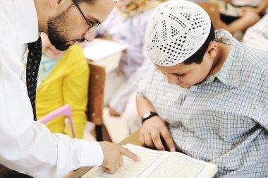 Children at school classroom, reading Koran