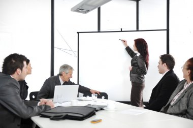 Business woman drawing a graph on whiteboard during the presentation at office