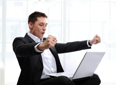 Happy executive raising fists in excitement, in front of laptop