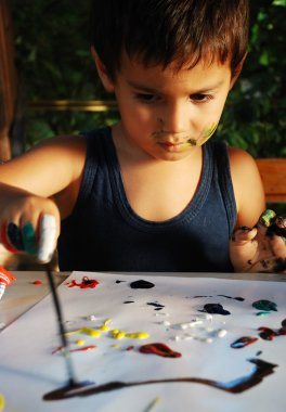 Little cute kid is playing with colors