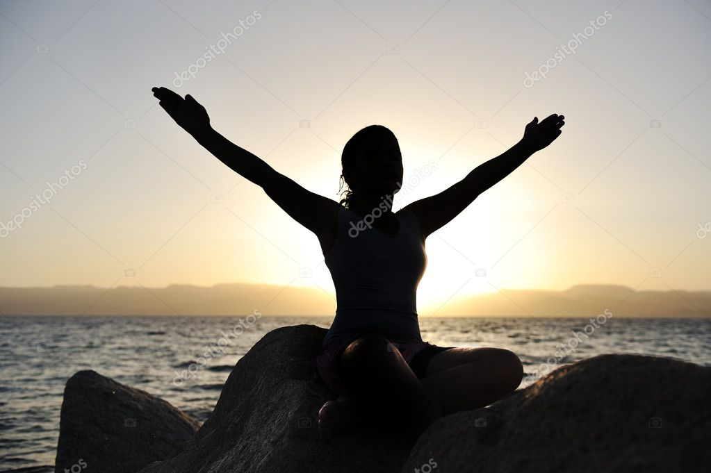 Silhouette of a beatiful female meditating on a rock by the sea