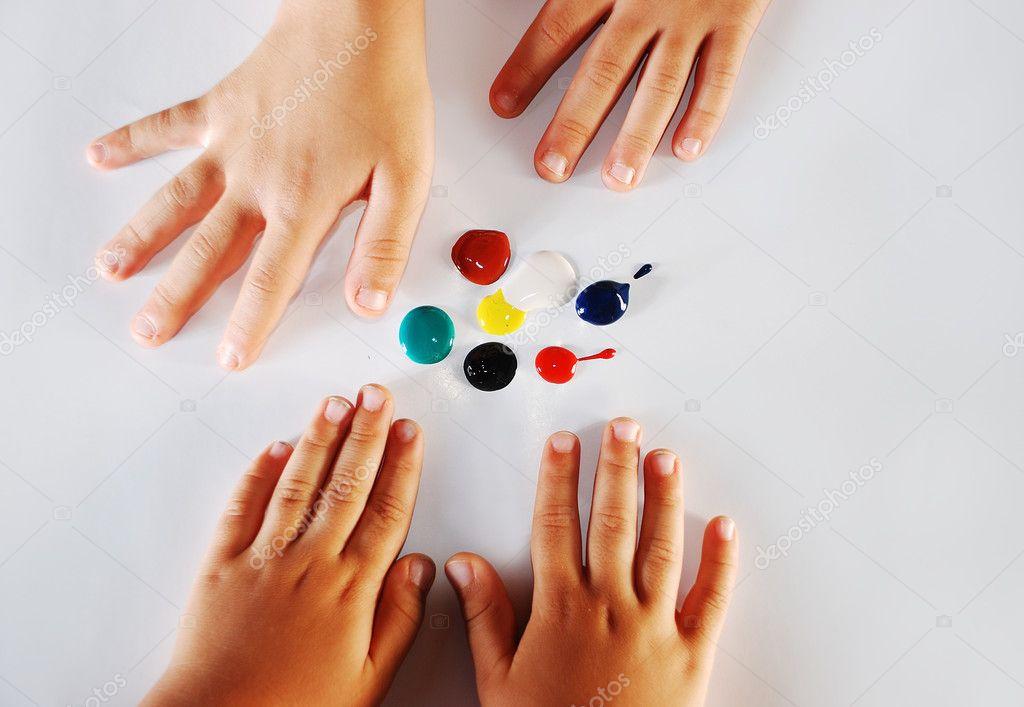 Kinder, die wenig Hände spielen mit Farben auf weißem Hintergrund ...