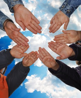 Many little children hands agains blue sky