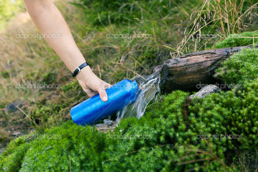 Woman taking water from spring