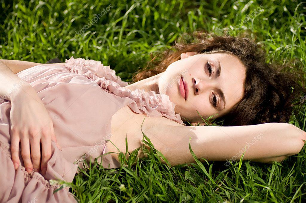 Beautiful woman in spring green grass
