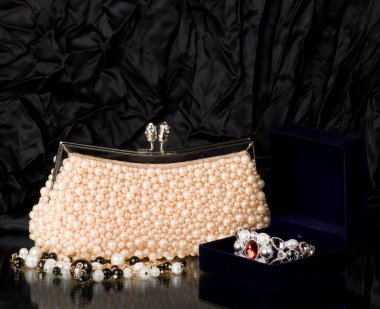 Sexy fashionable handbag with pearl jewelry on black background.
