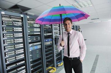 Businessman hold umbrella in server room