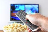 Fényképek távirányító a kéz ellen a pattogatott kukorica és a tv-készülék
