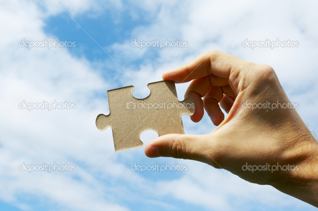 The hand holds puzzle on a background of the sky