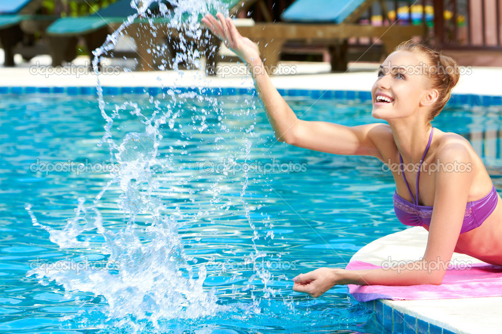 Happy woman splashing water in pool