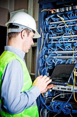Engineer in network server room solving problems