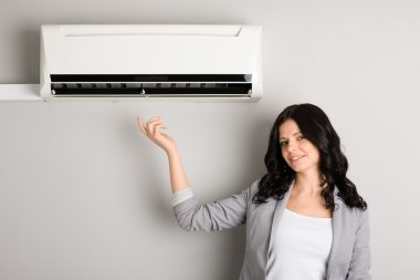 Young woman showing air conditioner