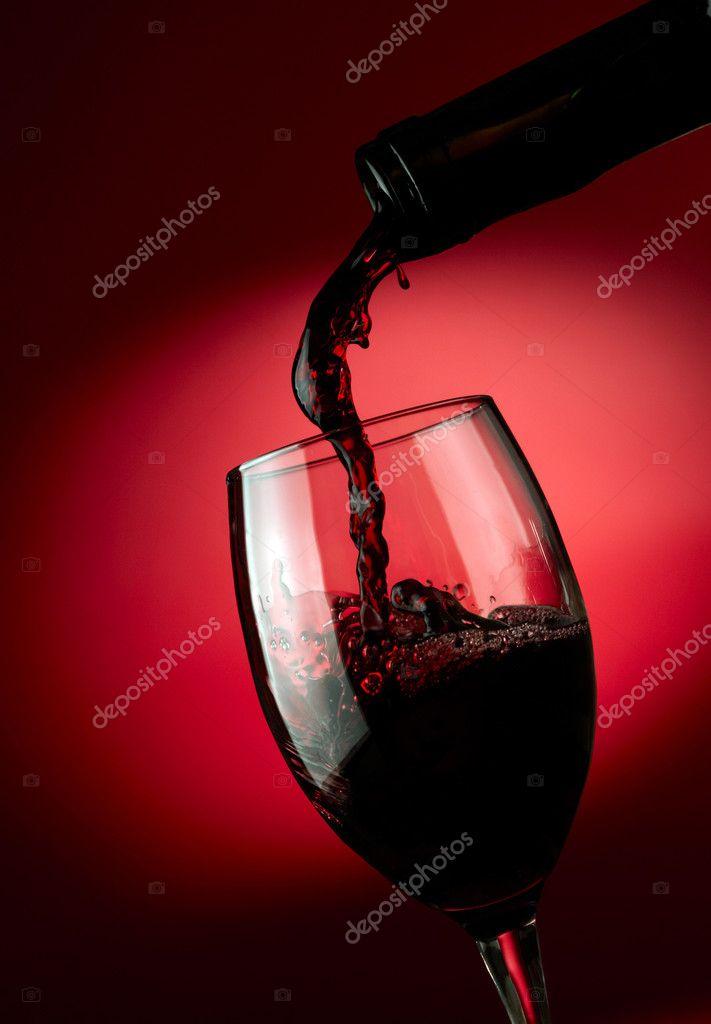 Vino Rosso Versando In Vetro Su Sfondo Scuro Foto Stock