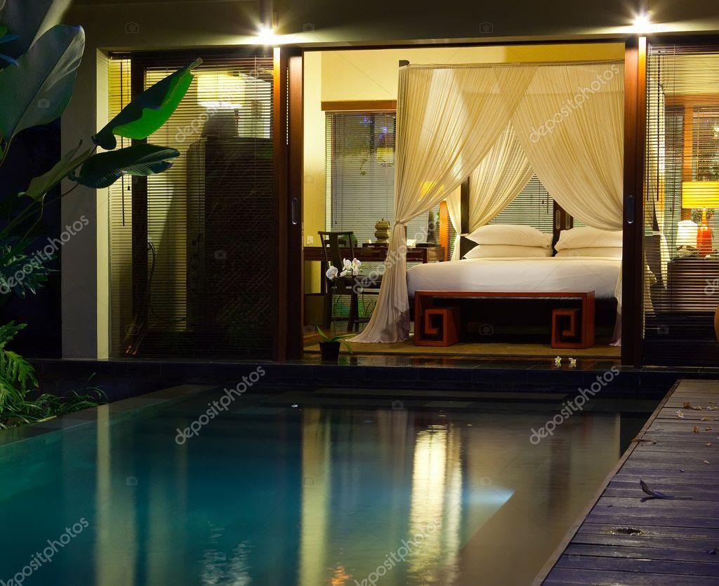 nacht zwembad en bed onder bed gordijnen stockfoto