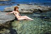 Mladá krásná žena v přírodní mořské plovárnu mezi kameny
