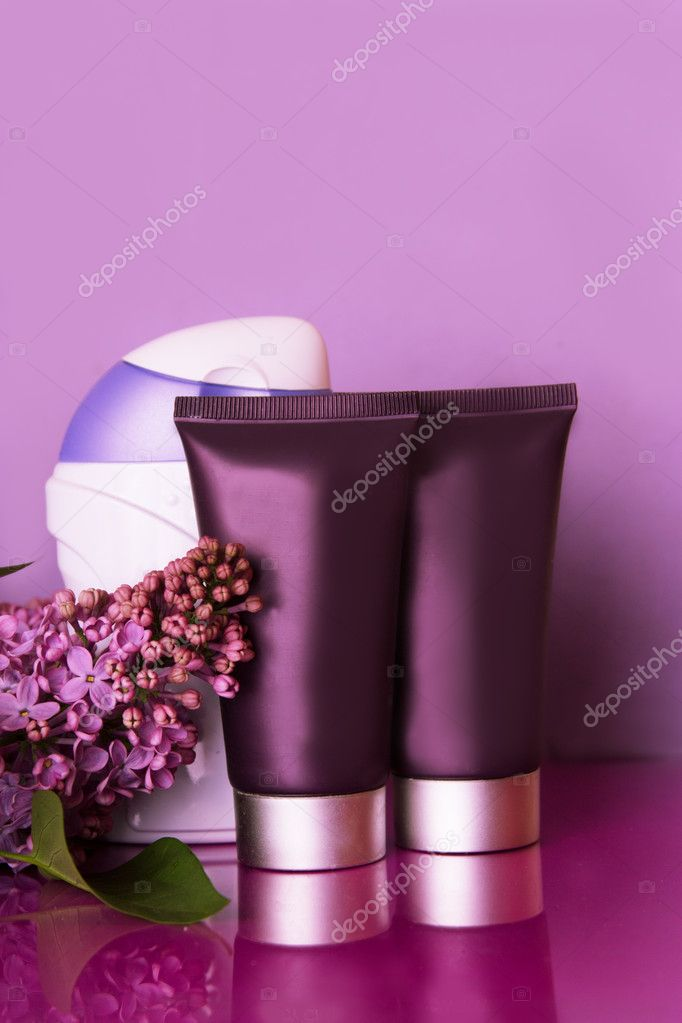 Bottles of cosmetics with lilac flowers