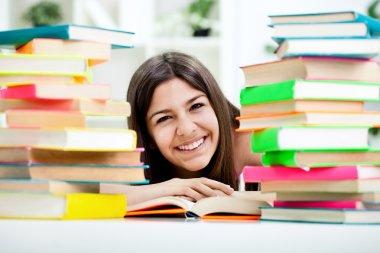 Teenage girl between stack of book