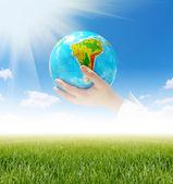 Globe kezében kék ég alatt