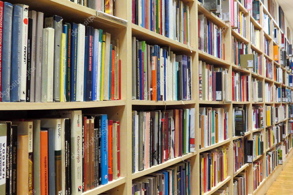 Книжная полка в библиотеке с много книг.