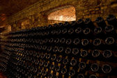 Photo Stacked up wine bottles in the cellar
