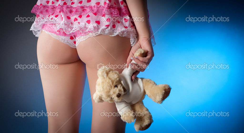 Young woman in lingerie holding a teddy bear